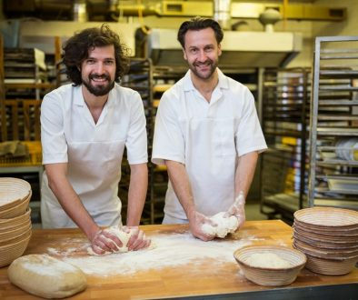 Two smiling bakers kneading dough on the counter